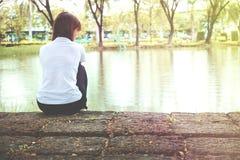 Einsame Frau, die auf einem hölzernen einsamen sitzt Stockbilder