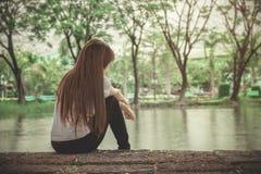 Einsame Frau, die auf einem hölzernen einsamen sitzt Stockfotos