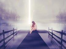 Einsame Frau, die auf Pier mit dem Ball des Glühens hell in ihrer Hand sitzt stockfoto