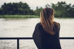 Einsame Frau, die den Fluss betrachtet stockfoto
