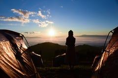 Einsame Frau, die den Sonnenaufgang aufpasst Stockbild