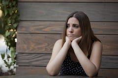 Einsame Frau, die in der hölzernen Kaffeestube sitzt Stockfoto