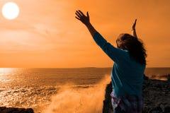 Einsame Frau, die eine leistungsfähige riesige Welle im sunshi gegenüberstellt Stockbilder