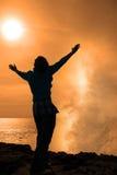 Einsame Frau, die eine leistungsfähige Welle im Sonnenschein gegenüberstellt Stockbilder
