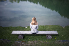 Einsame Frau, die am See sitzt Lizenzfreie Stockbilder