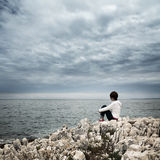 Einsame Frau, die in stürmischem Meer sitzt lizenzfreie stockbilder