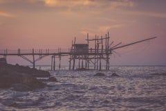 Einsame Frau, die an trabocchi Pier am nostalgischen Abend steht Stockfoto