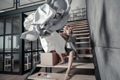 Einsame Frau, die zu Hause auf Treppe und werfender Kleidung sitzt stockbilder