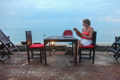 Einsame Frau in einem Café auf dem Strand ein Menü lesend Stockfotos