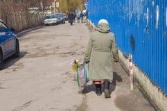 Einsame Frau geht auf eine tragende Handtasche der Straße mit Blumenstrauß Lizenzfreies Stockbild