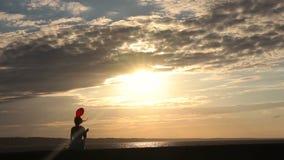 Einsame Frau mit aufpassendem Sonnenuntergang des Herzballons stock footage