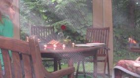 Einsame Frau sitzen nahe Tabelle mit Brandkerze und trinken in der Laube stock video