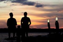 Einsame Frau zwei, die auf einem Holzbrückesonnenuntergang sitzt seien Sie einsam Abstrakte Schatten der Art Schattenbild Stockfotos