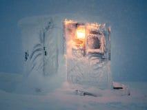 Einsame gefrorene und schneebedeckte Kabine mit leuchtender Straßenlaterne während des Blizzards nachts Lizenzfreie Stockfotos