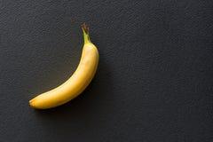 Einsame gelbe Banane auf einem schwarzen Hintergrund Stockfoto
