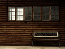 Einsame hölzerne Bank mit Windows Stockfotografie