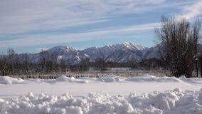 Einsame Hügel und Bergkuppen Berge unter dem Schnee und dem eisigen kalten blauen Himmel stock video footage
