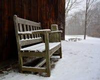Einsame Holzbank vor Scheune während des Schneesturmes Stockfoto