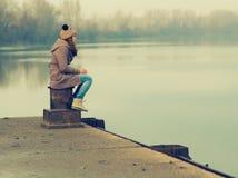 Einsame Jugendliche, die auf dem Dock sitzt Stockfotografie