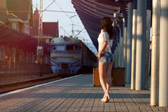 Einsame junge Brunettefrau, in den sexy kurzen Hosen mit altem Koffer an Stockfotografie