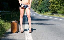 Einsame junge Brunettefrau, die auf der Seite der Straße mit einem alten Koffer gehen und ein Zeichen für das Per Anhalter fahren Lizenzfreies Stockfoto
