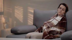 Einsame junge deprimierte Frau, die auf der Couch, bedeckt mit Plaid, Verzweiflung schl?ft lizenzfreie stockbilder