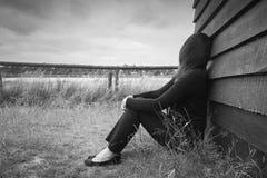 Einsame junge deprimierte traurige Frau, die an einer hölzernen Hütte anstarrt in den Abstand sich lehnt Lizenzfreie Stockfotografie