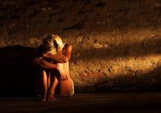 Einsame junge Frau, die auf der Straße sitzt Stockfoto
