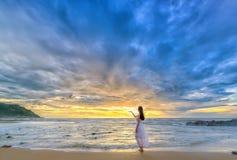 Einsame junge Frau steht allein auf dem Strand, der in Richtung des Endes des beträchtlichen Horizontes blickt lizenzfreie stockbilder
