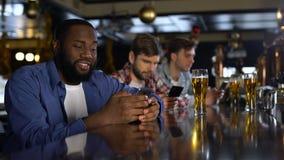 Einsame Männer, die in der Kneipe, schauend durch die Datierung von Standorten in den Mobiltelefonen, Sucht sitzen stock video footage