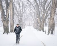 Einsame Männerfigur, die in einen Blizzard geht Lizenzfreie Stockbilder