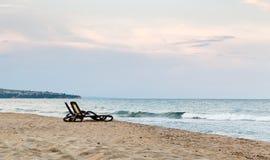 Einsame Paare Strand deckchairs auf Küste vor Meer, Sonnenuntergang lizenzfreies stockfoto