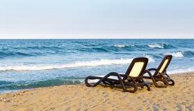 Einsame Paare Strand deckchairs auf Küste vor Meer, Sonnenuntergang lizenzfreie stockfotografie