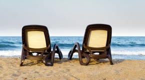 Einsame Paare Strand deckchairs auf Küste vor Meer, Sonnenuntergang, Abschluss oben stockbild
