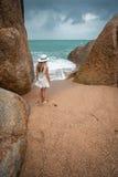 Einsame schlanke Frau auf einem einsamen Strand auf dem Hintergrund von großen Steinen und von bewölkten Himmel Stockfotos