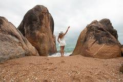 Einsame schlanke Frau auf einem einsamen Strand auf dem Hintergrund von großen Steinen und von bewölkten Himmel Sie stellt zum Me Lizenzfreie Stockfotografie
