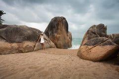 Einsame schlanke Frau auf einem einsamen Strand auf dem Hintergrund von großen Steinen und von dunklen bewölkten Himmel Lizenzfreies Stockbild