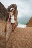 Einsame schlanke Frau auf einem einsamen Strand auf dem Hintergrund von großen Steinen und von dunklen bewölkten Himmel Stockbild