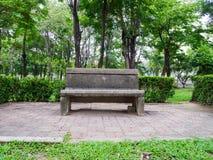 Einsame Steinbank in der grünen Parkumwelt Stockfotos