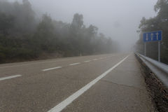 Einsame Straße im Nebel Lizenzfreies Stockbild
