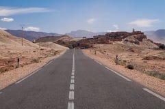 Einsame Straße zu einem kleinen Dorf in der Wüste von Marokko lizenzfreie stockfotografie