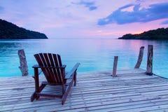 Einsame Szene; Einzelner Holzstuhl im Hafen über Meer am twili Stockbild