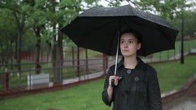 Einsame traurige Frau geht hinunter die Straße im starken Regen Langsame Bewegung stock video