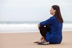 Einsame und deprimierte Frau, die auf dem Sand eines einsamen Strandes sitzt Lizenzfreie Stockbilder
