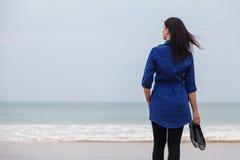 Einsame und deprimierte Frau, die vor dem Meer steht Lizenzfreies Stockbild