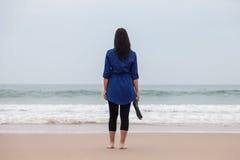 Einsame und deprimierte Frau, die vor dem Meer steht Stockbilder