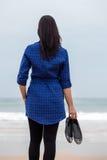 Einsame und deprimierte Frau, die vor dem Meer steht Lizenzfreies Stockfoto