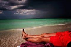 Einsame und erfolgreiche Männer, die auf dem Strand in Kuba liegen Lizenzfreies Stockfoto