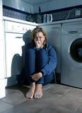 Einsame und kranke Frau, die auf Küchenboden in der Druckkrise und in der Traurigkeit schreit Stockfotografie