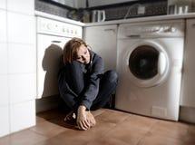 Einsame und kranke Frau, die auf Küchenboden in der Druckkrise und in der Traurigkeit sitzt Stockfoto